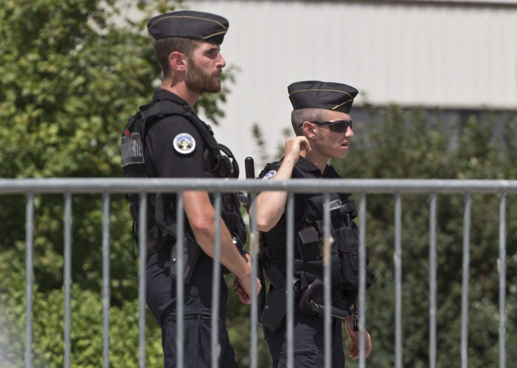 Police officers guard a road leading to a plant which was attacked on Friday in Saint-Quentin-Fallavier, southeast of Lyon, France, Saturday, June 27, 2015. A spokeswoman for the Paris prosecutor's office says one of the four suspects detained over an explosion and beheading in southeast France has been released, while the suspected assassin isn't speaking to investigators. (AP Photo/Michel Euler)