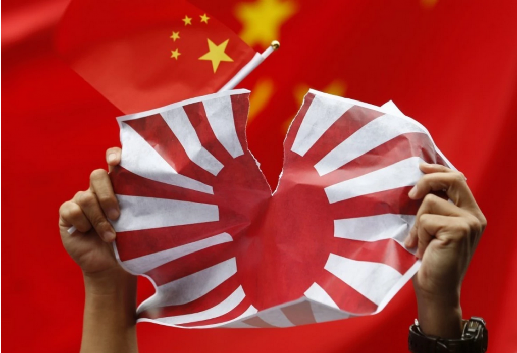 An anti-Japan protester tears a Japanese Rising Sun flag during a rally outside the Japanese Consulate General in Hong Kong on Aug. 16, 2012. Protesters were demanding that the Japanese government release Chinese activists arrested in Japan after landing on Uotsuri Island, one of the islands of disputed territory between the two countries. (Kin Cheung/AP)