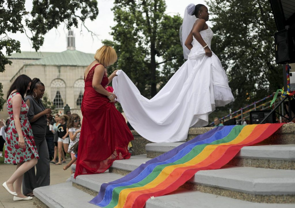 Catrina Burks is assisted up the steps in Bronson Park before Rev. Nathan Dannison unites her and her wife Marashette Burks in marriage in Kalamazoo, Mich. on Friday, June 26, 2015. Friday's U.S. Supreme Court ruling legalizes gay marriage nationwide. (Daytona Niles/Kalamazoo Gazette via AP)
