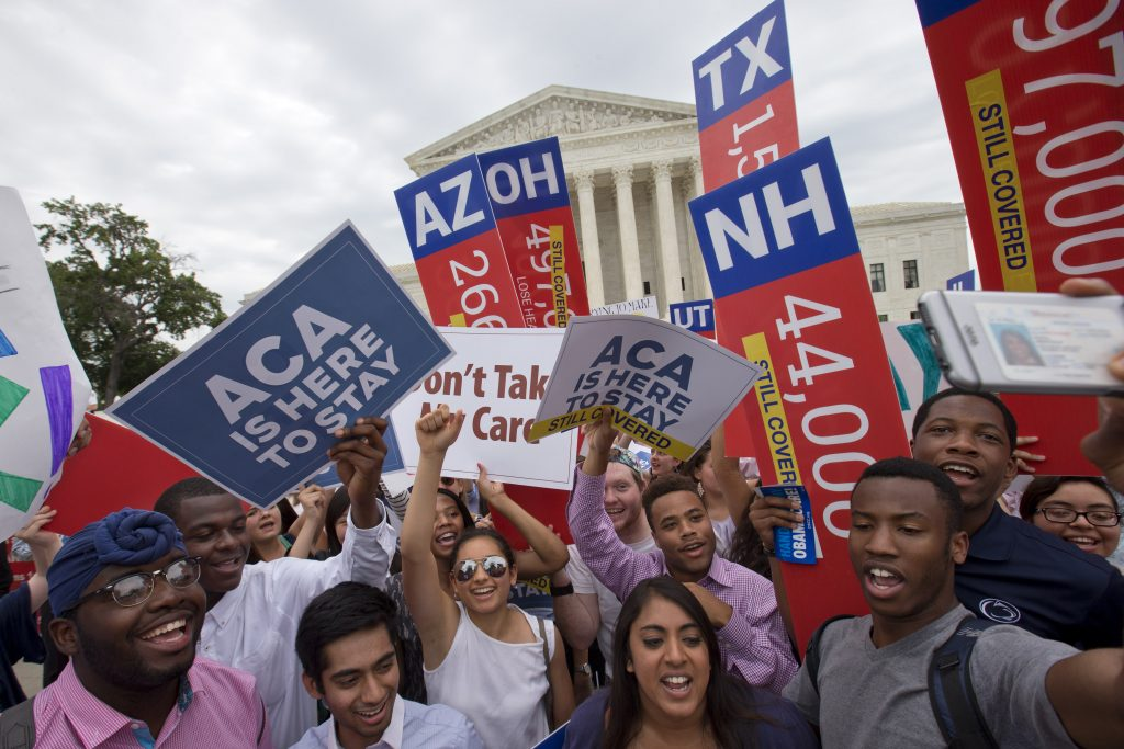 "Students cheer as they hold up signs indicating the numbers of people in different states who would lose healthcare coverage,  now over written with ""still covered"" stickers, after the Supreme Court decided that  the Affordable Care Act (ACA) may provide nationwide tax subsidies, Thursday June 25, 2015, outside of the Supreme Court in Washington. (AP Photo/Jacquelyn Martin)"