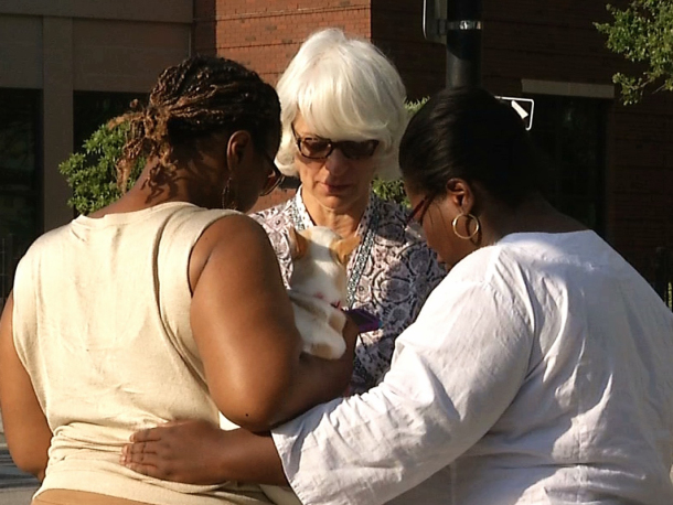 Tarsha Moseley, left, Martha Watson and Toby Smith pray Thursday at a makeshift memorial near the Emanuel African Methodist Episcopal Church in Charleston, South Carolina. (AP Photo/Alex Sanz)