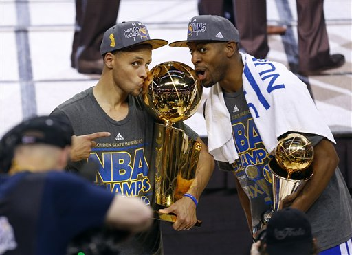 Golden State Warriors guard Stephen Curry, left, holds the championship trophy and Andre Iguodala holds the series MVP trophy as they celebrate winning the NBA Finals against the Cleveland Cavaliers in Cleveland, Wednesday, June 17, 2015. The Warriors defeated the Cavaliers 105-97 to win the best-of-seven game series 4-2. (AP Photo/Paul Sancya)