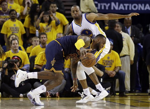 Cleveland Cavaliers forward LeBron James, bottom, drives against Golden State Warriors forward Andre Iguodala during overtime of Game 1 of basketball's NBA Finals in Oakland, Calif., Thursday, June 4, 2015. (AP Photo/Ben Margot)