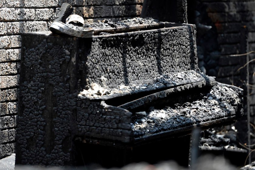 A destroyed piano is part of the charred remains of Briar Creek Road Baptist Church Wednesday, June 24, 2015 in Charlotte, N.C.  Investigators with the Charlotte Fire Department say a fire at the predominantly black church is a case of arson. The church's congregation is predominantly black, and there are about 100 members. Investigators are not sure if the fire was racially motivated.  (Davie Hinshaw/The Charlotte Observer via AP)