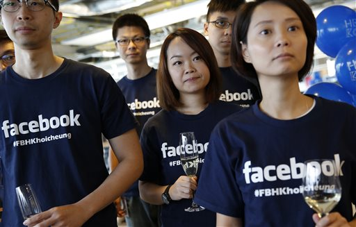 In this July 24, 2014 file photo, Facebook staff members attend the opening ceremony of their new office in Hong Kong. The world's biggest online social network knocked Wal-Mart, the world's largest retailer, out of the top 10 list of the highest-valued companies in the Standard & Poor's 500 index on Monday, June 22, 2015, and the gap widened on Tuesday. (AP Photo/Kin Cheung, File)