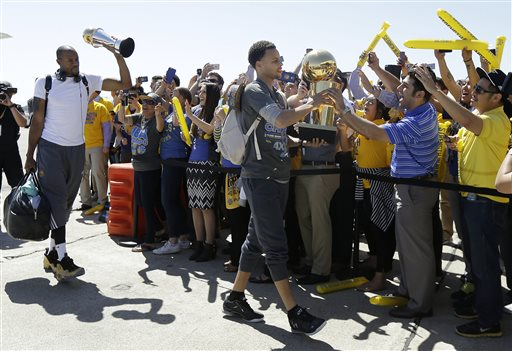 Golden State Warriors guard Stephen Curry, center, walks past cheering team employees as he carries the Larry O'Brien championship trophy in front of forward Andre Iguodala, lifting the NBA Finals MVP trophy, after the team landed in Oakland, Calif., Wednesday, June 17, 2015. The Warriors beat the Cleveland Cavaliers to win their first NBA championship since 1975. (AP Photo/Jeff Chiu)