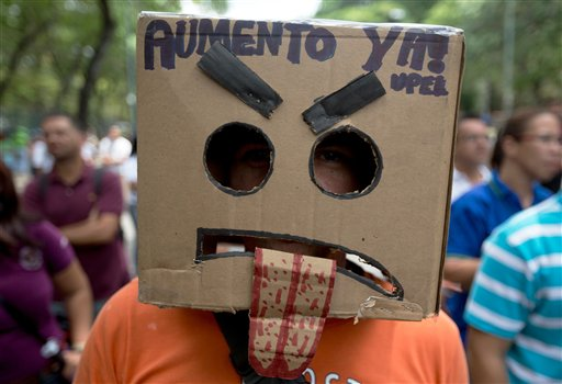 "In this Thursday, May 28, 2015 photo, a teacher with the head covered by a box with a sign that  reads in Spanish ""Salary raise now"" during a protest at Venezuela's Central University, UCV, in Caracas, Venezuela. More than 700 of the 4,000 professors who once taught at the highly respected Central University have quit during the last four years, some taking better-paying jobs in other fields inside the country while others have been lured to more attractive academic posts at universities abroad. (AP Photo/Fernando Llano)"