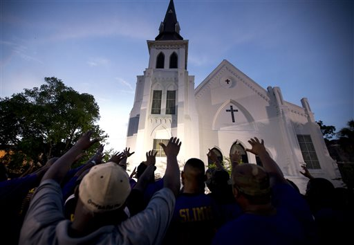 The men of Omega Psi Phi Fraternity Inc. lead a crowd of people in prayer outside the Emanuel AME Church, Friday, June 19, 2015, after a memorial in Charleston, S.C. Thousands gathered at the College of Charleston TD Arena to bring the community together after nine people where shot to death at the church on Wednesday. (AP Photo/Stephen B. Morton)