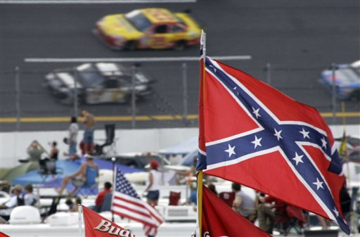 In this Oct. 7, 2007, file photo, a Confederate flags fly in the infield as cars come out of turn one during a NASCAR auto race at Talladega Superspeedway in Talladega, Ala. NASCAR is backing South Carolina Gov. Nikki Haley's call to remove the Confederate flag from the South Carolina Statehouse grounds in the wake of a massacre at a Charleston church, it said in a statement Tuesday, June 23, 2015. Though NASCAR bars the use of the flag in any official capacity, many fans fly the flag at their races. (AP Photo/Rob Carr, File)