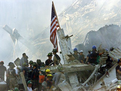 In this Sept. 13, 2001 file photo, an American flag flies over the rubble of the collapsed World Trade Center buidlings in New York. (AP Photo/Beth A. Keiser)
