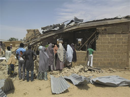 People gather at the site of suicide bomb attack at Redeem Christian church in Potiskum, Nigeria, Sunday, July 5, 2015.  Witnesses say a woman suicide bomber blew up in the midst of a crowded evangelical Christian church service on Sunday and killed at least five people, the latest in a string of bombings and shooting attacks blamed on the Islamic extremist group Boko Haram that has killed some 200 people in the past week. (AP Photo/Adamu Adamu)