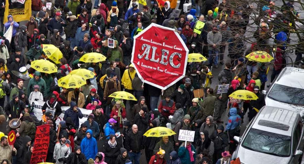 Occupy Portland F29 marchers walk up SW Broadway in Portland, Ore., Wednesday, Feb. 29, 2012. The march was to raise awareness of the American Legislative Exchange Council or ALEC. (AP Photo/The Oregonian, Benjamin Brink)