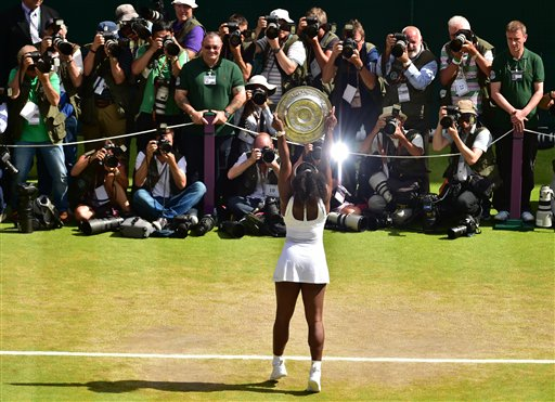 Serena Williams of the United States holds up the trophy toward the media after winning the women's singles final against Garbine Muguruza of Spain at the All England Lawn Tennis Championships in Wimbledon, London, Saturday July 11, 2015. (Dominic Lipinski/Pool Photo via AP)