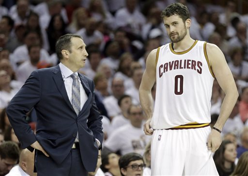 In this April 19, 2015, file photo, Cleveland Cavaliers head coach David Blatt, left, talks with Kevin Love (0) during an NBA playoff basketball game in Cleveland. A person familiar with the decision says Love has opted out of the final year of his contract and will be a free agent on July 1.  Love can test the market, where he will likely draw major interest, or stay in Cleveland and chase an NBA title with superstar LeBron James. (AP Photo/Mark Duncan, File)