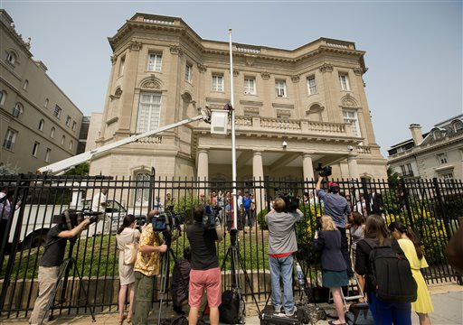 FILE - In this June 10, 2015 file photo, members of the media cover workers from Eastern Shores Flagpoles raising a flagpole at the Cuban Interest Section in Washington in preparation for re-opening of embassies in Havana and Washington. Cuba's blue, red and white-starred flag is set to fly Monday, July 20 outside the country's diplomatic mission in the United States for the first time since the countries severed ties in 1961. (AP Photo/Pablo Martinez Monsivais, File)
