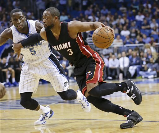 In this Feb. 25, 2015, file photo, Miami Heat's Dwyane Wade (3) goes to the basket past Orlando Magic's Victor Oladipo (5) during an NBA basketball game in Orlando, Fla. A person familiar with the negotiations says Wade is staying with the Heat. The person says Wade informed the Heat on Thursday, July 2, 2015, he will accept a one-year offer to re-sign for $20 million for next season. The person spoke to The Associated Press on condition of anonymity because no NBA deals can be finalized this summer until July 9. (AP Photo/John Raoux, File)