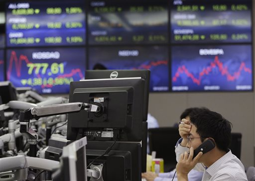 A currency trader speaks on the phone at the foreign exchange dealing room of the Korea Exchange Bank headquarters in Seoul, South Korea, Wednesday, July 22, 2015. Asian stock markets dropped Wednesday after U.S. earnings fell short of expectations and investors began to focus on next week's Federal Reserve meeting. (AP Photo/Ahn Young-joon)