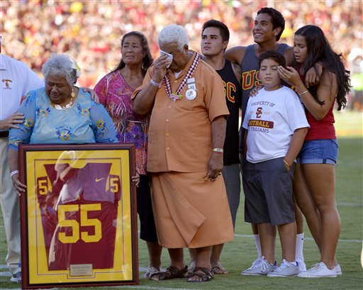 In this Sept. 1, 2012, file photo, family members of Junior Seau including his mother Luisa Seau, far left, and his father Tiaina Seau, third from left, stand during a ceremony to honor the former Southern California player during the first half of an NCAA college football game between Hawaii and Southern California in Los Angeles. The family of the late Junior Seau will not disrupt the Hall of Fame ceremonies on Aug. 8, 2015, despite their disagreement with a policy preventing live remarks during a posthumous induction. (AP Photo/Mark J. Terrill, File)