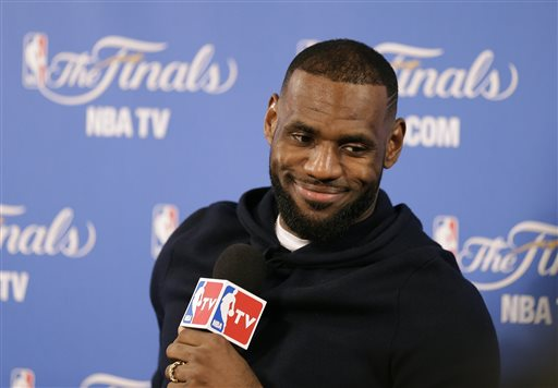 In this June 7, 2015, file photo, Cleveland Cavaliers forward LeBron James smiles during a news conference after Game 2 of basketball's NBA Finals in Oakland, Calif. Two people familiar with the negotiations say LeBron James has agreed to a one-year, $23 million contract with the Cavaliers for next season. The deal includes a player option for 2016-17. The people spoke to The Associated Press on condition of anonymity Thursday because the contract has not been signed. James has informed the team he will return. (AP Photo/Ben Margot, File)