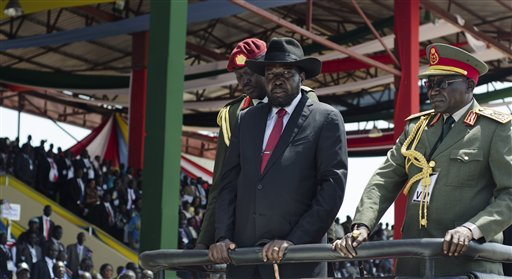 South Sudan's President Salva Kiir, center, accompanied by army chief of staff Paul Malong Awan, right, attends an independence day ceremony in the capital Juba, South Sudan, Thursday, July 9, 2015. South Sudan marked four years of independence from Sudan on Thursday, but the celebrations were tempered by concerns about ongoing violence and the threat of famine. (AP Photo/Jason Patinkin)