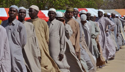 Men who were being detained on suspicion of affiliation to Boko Haram, line up as they are released by the Nigerian military in Maiduguri, Nigeria, Monday, July 6, 2015. Nigeria's military freed 180 detainees who had been held for up to two years, accused of being Boko Haram members. Those freed Monday included women with babies and toddlers. (AP Photo/Jossy Ola)