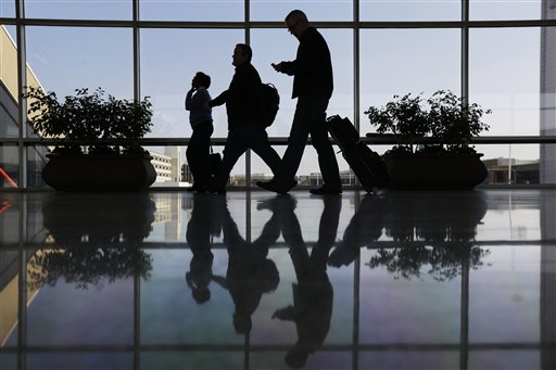 In this Feb. 14, 2013 file photo, Travelers pass through a corridor at Philadelphia International Airport in Philadelphia. The U.S. government is investigating possible collusion between major airlines to limit available seats, which keeps airfares high, according to a document obtained by The Associated Press. The civil antitrust investigation by the Justice Department appears to focus on whether airlines illegally signaled to each other how quickly they would add new flights, routes and extra seats. (AP Photo/Matt Rourke, File)