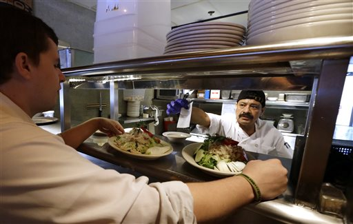 In this photo taken Monday, July 27, 2015, cook Bulmaro Sosa, right, goes over a food order with server Zachary DeYoung at an Ivar's restaurant in Seattle. After Seattle's new minimum wage law took effect last April 1, Ivar's Seafood Restaurants announced that it was jacking up its prices by about 21 percent, eliminating tipping as a routine procedure, and immediately paying all its hourly workers a $15 per hour. They began the new pay rate three years earlier than the law required. (AP Photo/Elaine Thompson)