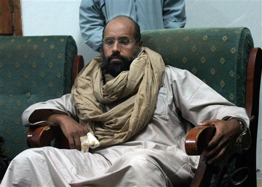 In this Saturday, Nov. 19, 2011 file photo, Seif al-Islam is seen after his capture in the custody of revolutionary fighters in Zintan. A court in the Libyan capital has sentenced Seif al-Islam to death over killings during the country's 2011 uprising. The Tripoli court handed down the sentence Tuesday for Seif al-Islam, who is currently being held by a militia that refuses to hand him over to the central government. The court sentenced eight others to death as well, including former Libyan spy chief Abdullah al-Senoussi. (AP Photo/Ammar El-Darwish, File)