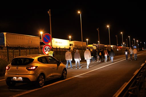 A car of the security society of Eurotunnel follows a group of migrants, in Calais, northern France, Wednesday, July 29, 2015. About 2,100 migrants tried to storm the area surrounding the Eurotunnel early Tuesday before being repelled by police, an official in the northern French port of Calais said. (AP Photo/Thibault Camus)