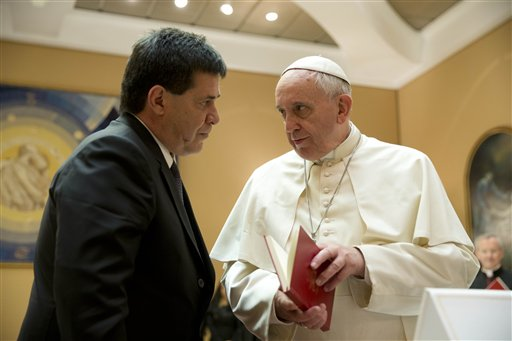 "In this April 29, 2014 file photo, Pope Francis presents Paraguay's President Horacio Cartes with the book of the gospel during a private audience at the Vatican. Pope Francis is taking his ""church for the poor"" to three of South America's poorest and most peripheral countries, making a grueling, week-long trip that will showcase the pope at his unpredictable best: speaking his native Spanish on his home turf about issues closest to his heart. (AP Photo/Gregorio Borgia, Pool, File)"