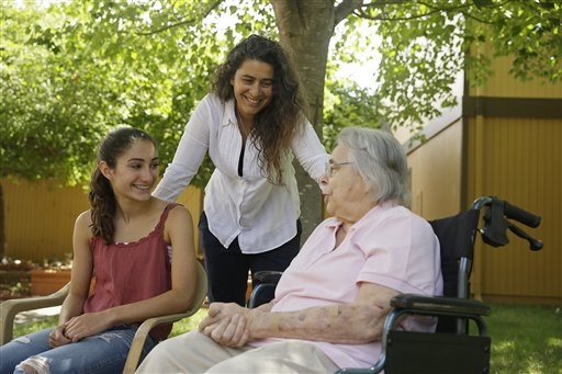 In this photo taken Monday, July 6, 2015, Kamila Al-Najjar, center, visits with her mother, Joan Groen, right, at her assisted living facility as her daughter, Inanna Al-Najjar, 14, left, looks on in Santa Rosa, Calif.  Caught between kids and aging parents, a new poll shows the sandwich generation worries more than most Americans their age about how they'll afford their own care as they grow older.  (AP Photo/Eric Risberg)