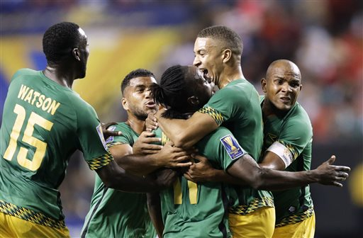 Jamaica's Darren Mattocks, center, is embraced by teammate Michael Hector, right, after Mattocks scored a goal during the first half of a CONCACAF Gold Cup soccer semifinal against the United States on Wednesday, July 22, 2015, in Atlanta. (AP Photo/David Goldman)