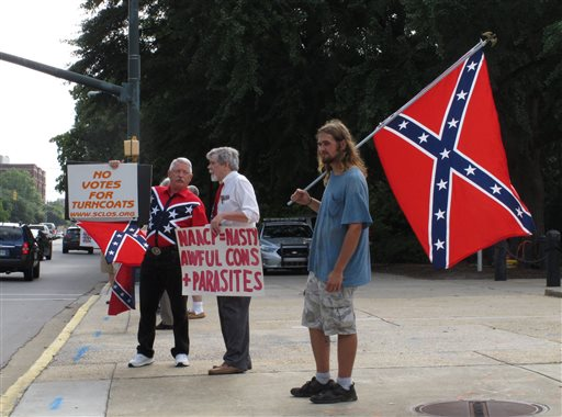 William Cheek, left, Nelson Waller, center, and Jim Collins, right, protest proposals to remove the Confederate flag from the grounds of the South Carolina Statehouse on Monday, July 6, 2015, in Columbia, S.C. The General Assembly returns Monday to discuss Gov. Nikki Haley's budget vetoes and what to do with the rebel flag that has flown over some part of the Statehouse for more than 50 years. (AP Photo/Jeffrey Collins)