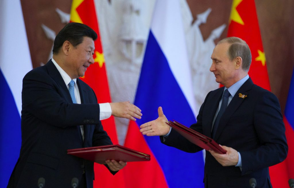 Russian President Vladimir Putin, right, and Chinese President Xi Jinping exchange documents at the signing ceremony in the Kremlin in Moscow, Friday, May 8, 2015. Russian and Chinese leaders have signed a plethora of deals in Moscow, giving Russia billions in infrastructure loans. (AP Photo/Alexander Zemlianichenko)