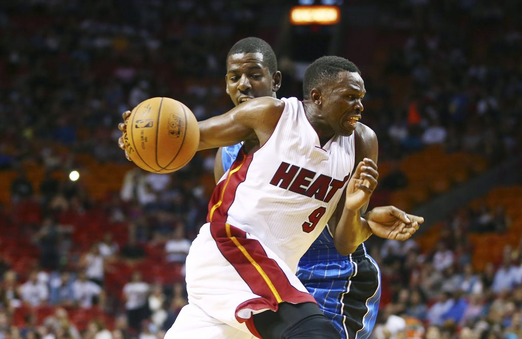 Miami Heat's Luol Deng (9) drives around Orlando Magic's Andrew Nicholson (44) during the first half of a NBA basketball game in Miami, Oct. 7, 2014. (AP Photo/J Pat Carter)