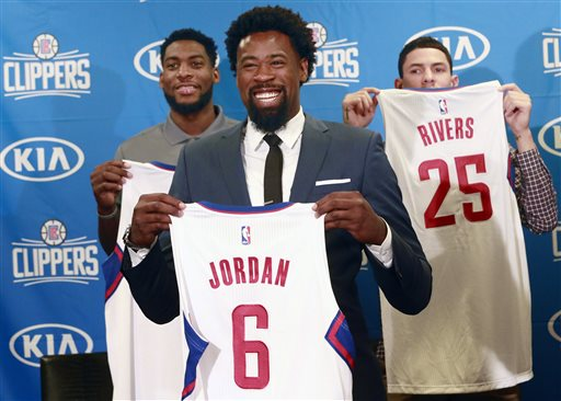 Los Angeles Clippers DeAndre Jordan, middle, the league rebounding champion, is reintroduced at a Staples Center news conference with teammates, forward Branden Dawson, left, and guard Austin Rivers, right, in Los Angeles on Tuesday, July 21, 2015.  The Clippers managed to keep Jordan after he changed his mind about his verbal commitment to Dallas Jordan thought the Dallas Mavericks offered everything he wanted, including a fresh start and a bigger offensive role. When Jordan thought about it a little more, the craziest free-agent recruitment story in recent NBA history ended with him back on the Los Angeles Clippers. (AP Photo/Nick Ut)