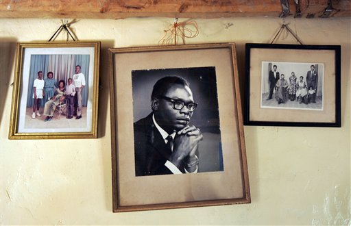 In this Thursday, Feb. 5, 2008 file photo, a photograph of Barack Obama Sr., father of President Barack Obama, hangs on the wall of his step-grandmother Sarah Obama's house in the village of Kogelo, near the shores of Lake Victoria, in Kenya. On Friday, July 24, 2015 Obama is due to arrive in Kenya, the country of his father's birth, for the first time since he was a U.S. senator in 2006, and the first stop on his two-nation African tour in which he will also visit Ethiopia. (AP Photo/Ben Curtis, File)