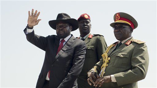 South Sudan's President Salva Kiir, left, accompanied by army chief of staff Paul Malong Awan, right, waves during an independence day ceremony in the capital Juba, South Sudan, Thursday, July 9, 2015. South Sudan marked four years of independence from Sudan on Thursday, but the celebrations were tempered by concerns about ongoing violence and the threat of famine. (AP Photo/Jason Patinkin)