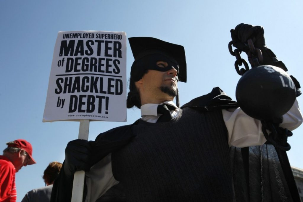 "In this Oct. 6, 2011 photo, Gan Golan of Los Angeles, dressed as the ""Master of Degrees,"" holds a ball and chain representing his college loan debt during Occupy DC activities in (AP Photo/Jacquelyn Martin)"