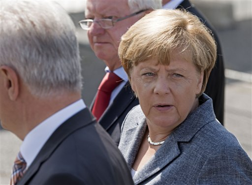 German Chancellor Angela Merkel arrives prior her visit  to a refugee shelter  that was attacked by far-right protesters over the weekend in Heidenau, eastern Germany, Wednesday, Aug. 26, 2015. Dozens of police were injured when a far-right mob hurled bottles and fireworks at officers in an attempt to prevent asylum seekers from moving into the former hardware store at the weekend. Germany has seen a surge in refugees coming to the country this year, with officials predicting the number could reach 800,000 by the end of 2015.  (AP Photo/Jens Meyer)