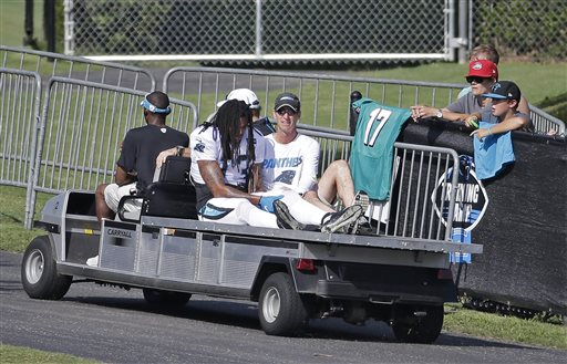 Carolina Panthers' Kelvin Benjamin (13) holds his left knee as he is carted off the field after being injured during a joint practice with the Miami Dolphins at NFL football training camp in Spartanburg, S.C., Wednesday, Aug. 19, 2015. (AP Photo/Chuck Burton)