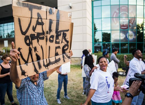 In this photo taken Tuesday, Aug. 11, 2015, Joe Barrientos holds a sign calling for a jail sentence for Arlington Police Officer Brad Miller during a protest outside the Arlington Police Department in Arlington, Texas, demanding that Miller be charged with a crime. Miller, who killed 19-year-old Christian Taylor, an unarmed college football player, during a suspected burglary at a Texas car dealership was fired Tuesday for making mistakes that the city's police chief said caused a deadly confrontation that put him and other officers in danger. (Ashley Landis/The Dallas Morning News via AP)