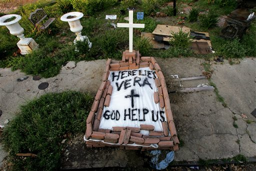 """In this Sept. 4, 2005, file photo, a makeshift tomb at a New Orleans street corner conceals a body that had been lying on the sidewalk for days in the wake of Hurricane Katrina. The message reads, """"Here lies Vera. God help us."""" Smith's cremated remains were later reburied in Texas, yet she remains part of her old community. (AP Photo/Dave Martin, File)"""