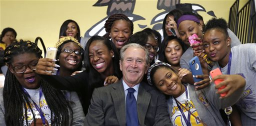Former President George W. Bush poses for photos with students at Warren Easton Charter High School in New Orleans, Friday, Aug. 28, 2015. Bush is in town to commemorate the 10th anniversary of Hurricane Katrina, which is Saturday. (AP Photo/Gerald Herbert)