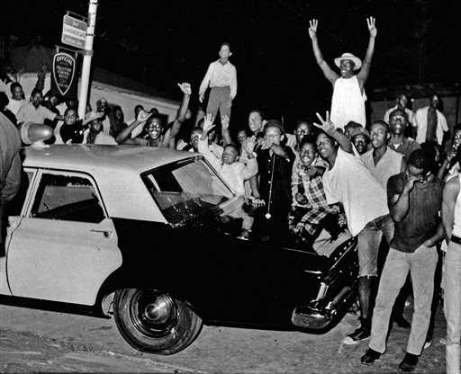 FILE - In this Aug. 12, 1965 file photo, demonstrators push against a police car after rioting erupted in the Watts district of Los Angeles. It began with a routine traffic stop 50 years ago this month, blossomed into a protest with the help of a rumor and escalated into the deadliest and most destructive riot Los Angeles had seen. The Watts riot broke out Aug. 11, 1965 and raged for most of a week. When the smoke cleared, 34 people were dead, more than a 1,000 were injured and some 600 buildings were damaged .(AP Photo, File)
