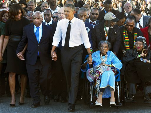 "In this March 7, 2015 file photo, President Barack Obama, center, holds hands with Rep. John Lewis, D-Ga., left, and Amelia Boynton Robinson, right, who were both beaten during ""Bloody Sunday,"" as they walk across the Edmund Pettus Bridge in Selma, Ala., for the 50th anniversary of ""Bloody Sunday."" Boynton Robinson, a civil rights activist who nearly died while helping lead the Selma march on ""Bloody Sunday,"" championed voting rights for blacks, and was the first black woman to run for Congress in Alabama, died Wednesday, Aug. 26, 2015. She was 104. Boynton Robinson was hospitalized in July after having a major stroke and turned 104 on Aug. 18. (AP Photo/Jacquelyn Martin, File)"