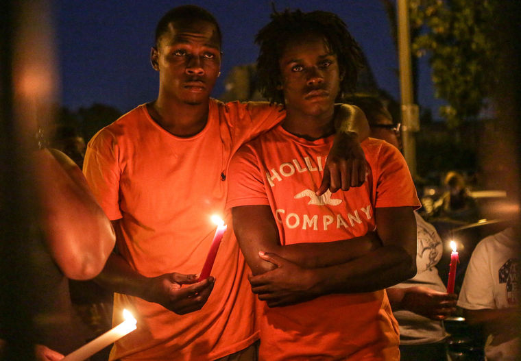 James Cody comforts his cousin Dennis Ball-Bey at a candlelight vigil held for Dennis' brother Mansur Ball-Bey, who was fatally wounded in an officer-involved shooting Wed. night in the Fountain Park neighborhood of St. Louis City. (Lawrence Bryant/St. Louis American)