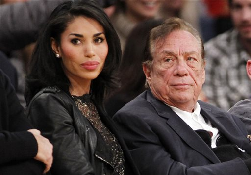 """In this Dec. 19, 2010, file photo, Los Angeles Clippers owner Donald Sterling, right, and V. Stiviano, left, watch the Clippers play the Los Angeles Lakers during an NBA preseason basketball game in Los Angeles. Sterling sued celebrity website TMZ and an ex-girlfriend over the recording of his off-color remarks that cost him ownership of the Los Angeles Clippers. Sterling's lawsuit filed Friday, Aug. 7, 2015, in Los Angeles Superior Court accused TMZ and V. Stiviano of violating his privacy and causing damage on a """"scale of unparalleled and unprecedented magnitude."""" (AP Photo/Danny Moloshok, File)"""