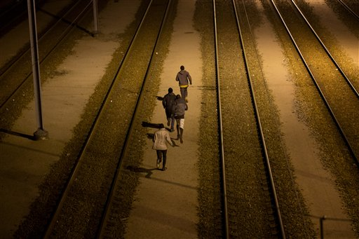 In this Tuesday, Aug. 4, 2015 file photo, migrants run a long the train track after crossing a fence as they attempt to access the Channel Tunnel in Calais, northern France. A gallery of images recounting the lives of some of the estimated 3,000 migrants who have gathered in the northern French port city of Calais, most feeding on the hope of sneaking across the English Channel to settle in Britain. (AP Photo/Emilio Morenatti, File)