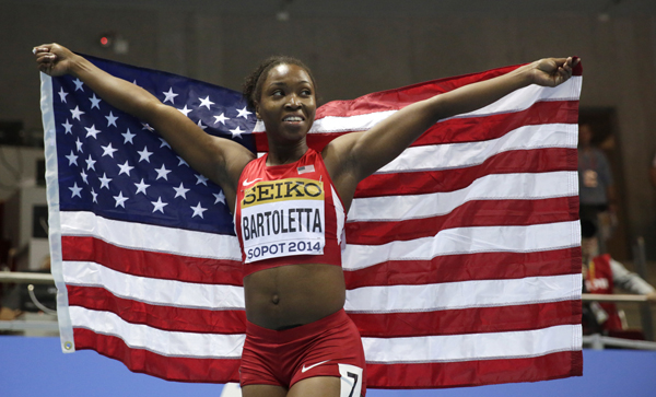 United States' Tianna Bartoletta celebrates with the US flag after winning the bronze in the women's 60m final during the Athletics Indoor World Championships in Sopot, Poland, Sunday, March 9, 2014. (AP Photo/Matt Dunham)